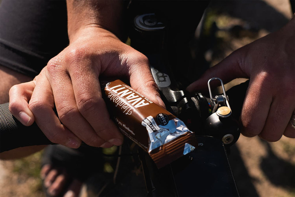 Man holding cycling energy bars whilst riding a bike