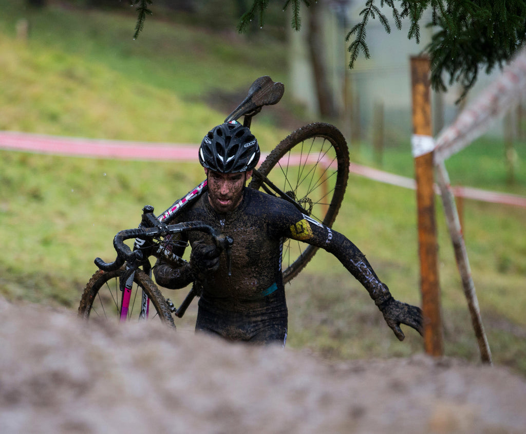 A cyclist is carrying a bike on his back while walking through mud.