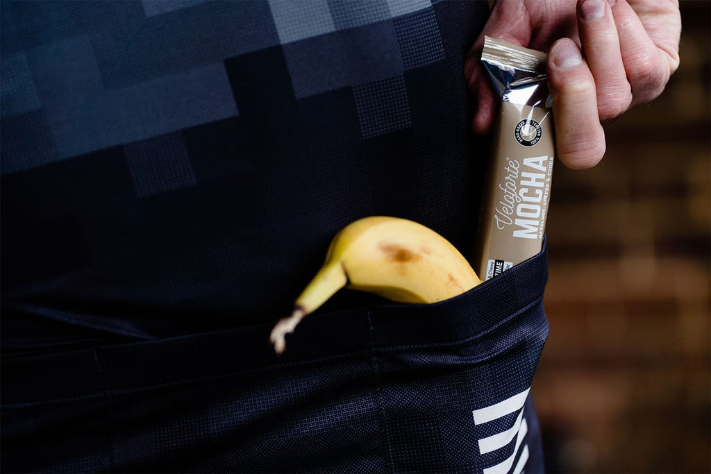 Man with cycling protein bar with banana in his pocket