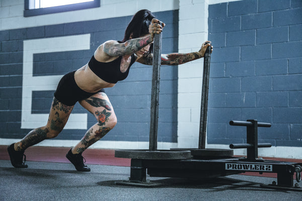 Tattooed woman doing the Prowler Sled Training in gym