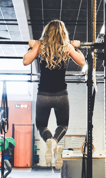 woman training on pull up bars in the gym