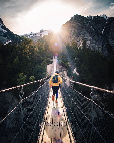 A person is running across a wooden bridge in the mountains.