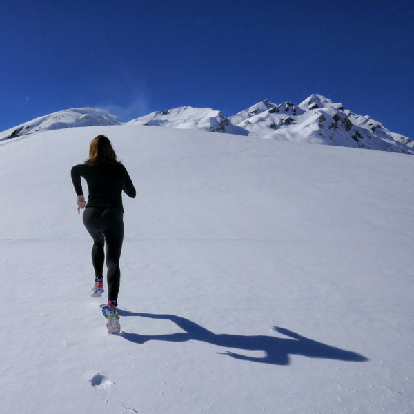 A woman is running upward the mountain during winter.