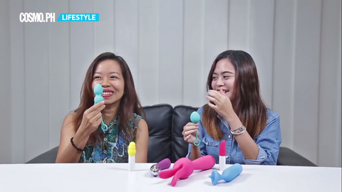 Two girls joke about the Tickler Trainer Kegel Exercise sex toy. They think it's a butt plug sex toy, but it's actually not; it's for the vaginal opening. Spread on the table before them are other sex toys, including bullet vibrator type sex toys, magic wand massager type sex toys, regular vibrator sex toys, and clitoris stimulating vibrator sex toys.
