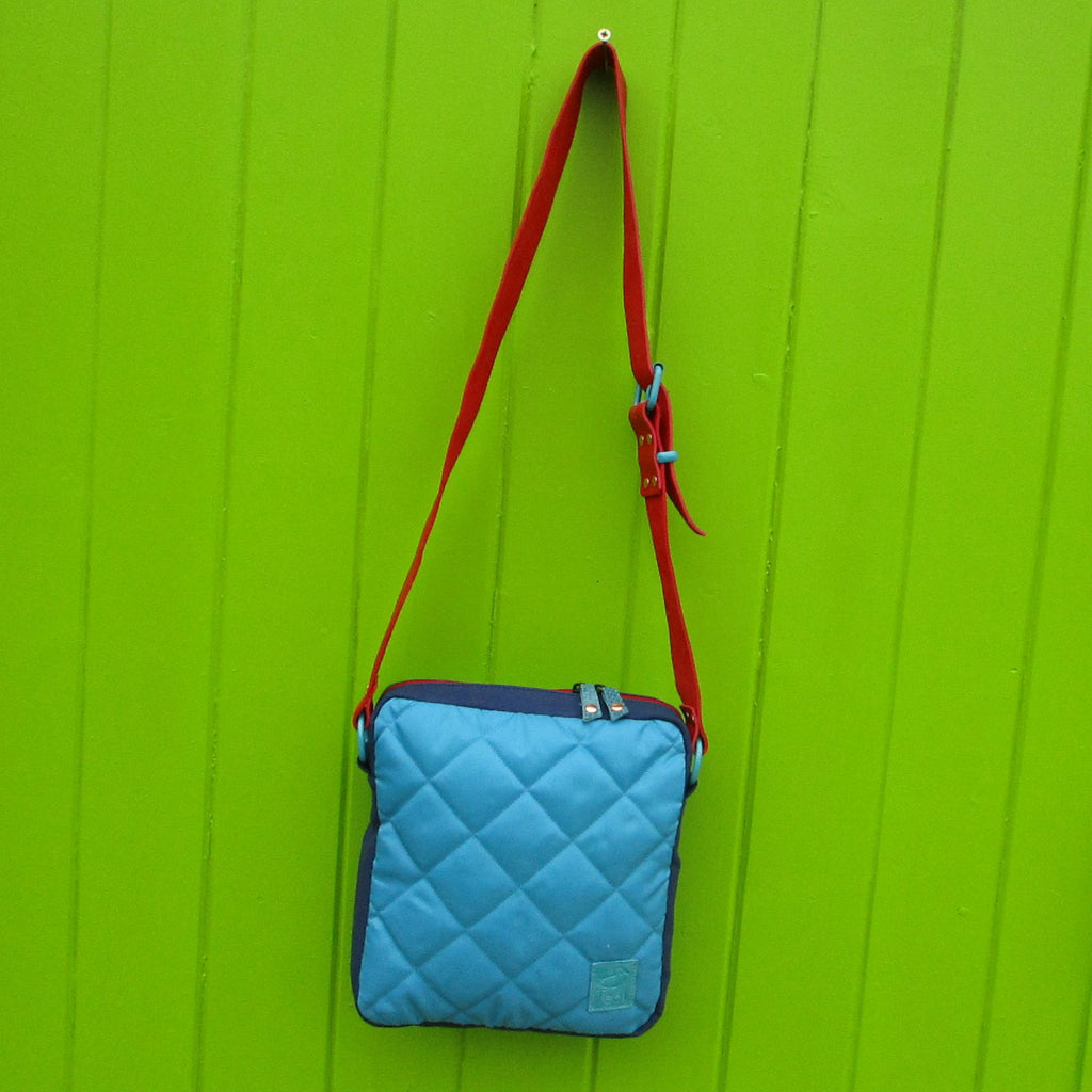 quilted day bag with red leather handle