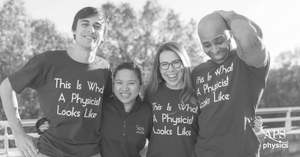 "Two men and two women standing in a row wearing shirts that say ""This is what a physicist looks like"""
