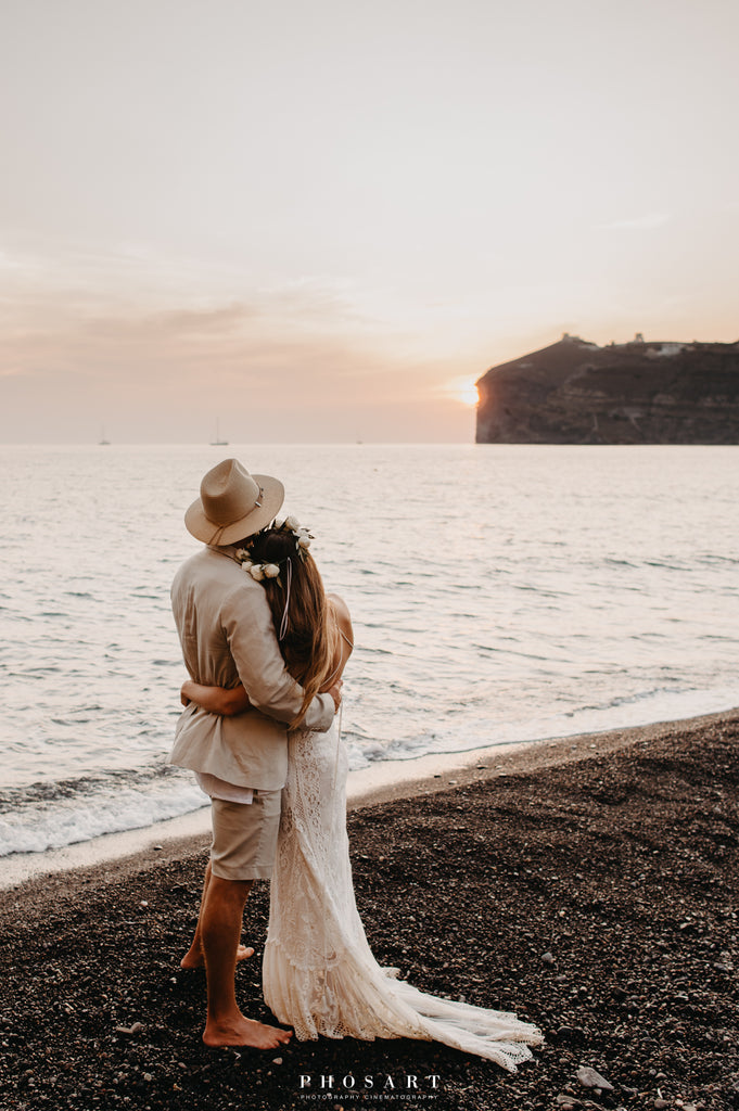 bohemian couple watching sunset on Santorini beach