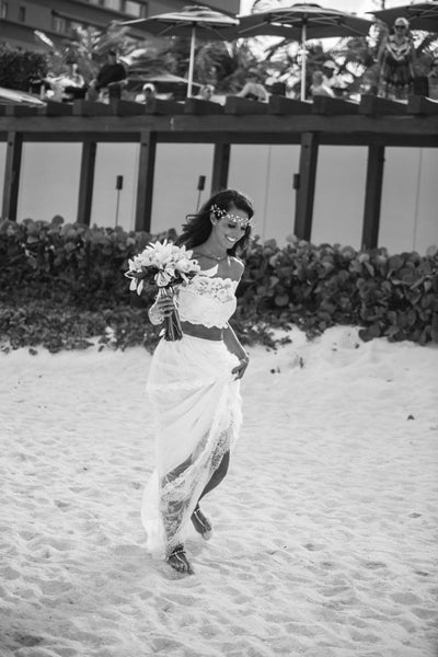 Beach bride in barefoot sandals and boho crop top wedding dress