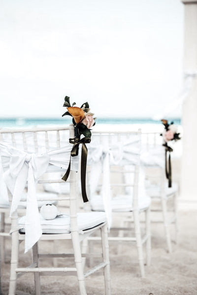 beach wedding aisle decor with white ribbon dusty rose and white flowers