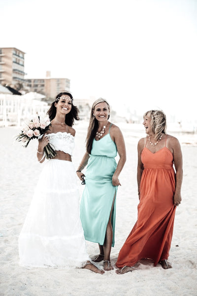 Beach Bride with her bridesmaids in their teal and coral dresses wearing foot jewelry