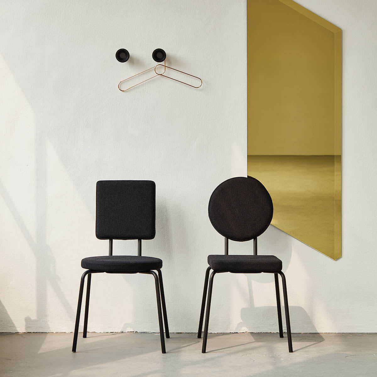 Gold Facett geometric design wall mirror with two black shape chairs
