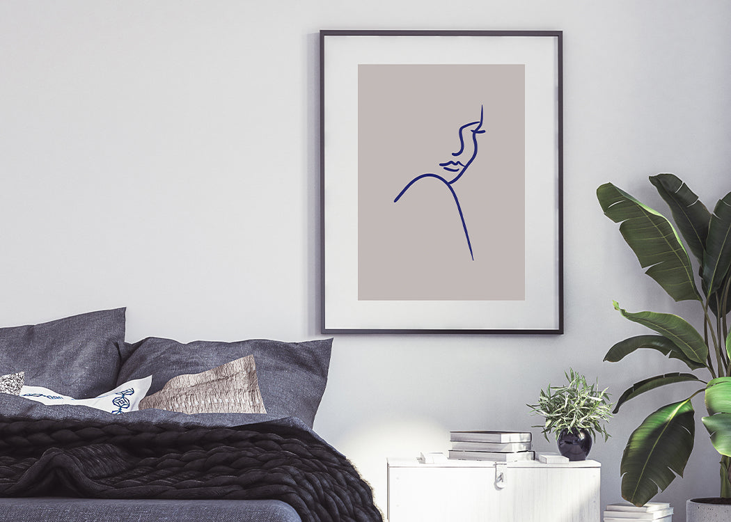 Framed Shoulder Art Print On A White Wall With Black Bed And Plant