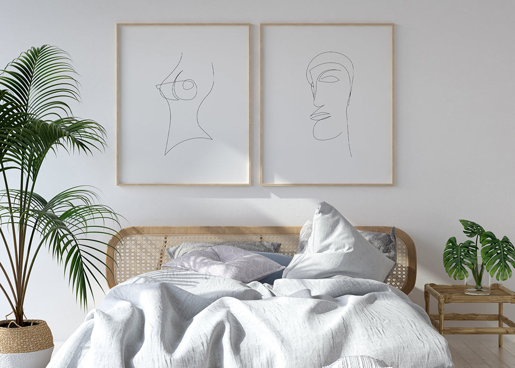 Framed Single Line Nude Art Print With 1 other Print On A White Wall And Black Sofa