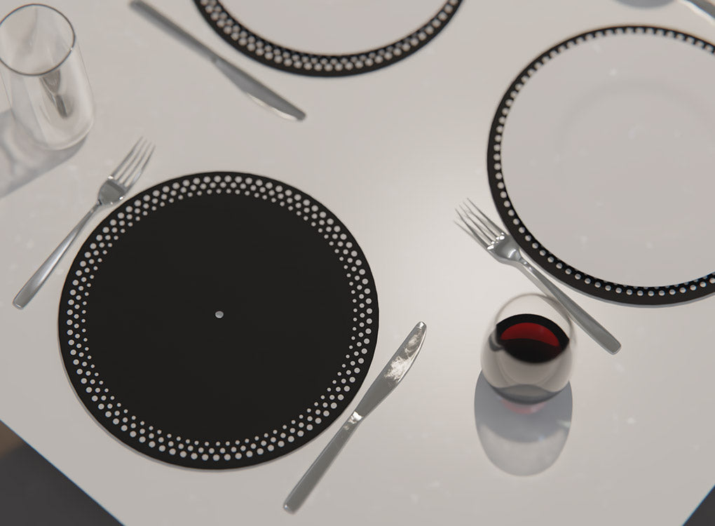 Pikkii DJ slipmat place mats on a dining table with a glass of wine