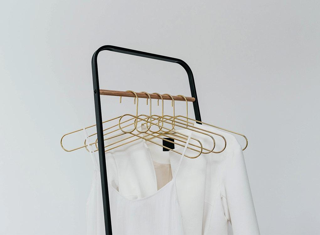gold loop hangers on a black and wooden rail hanging an cotton white shirt