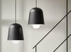 Two black cone light pendants hanging over stairs by Puik