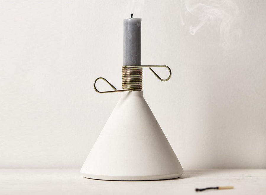 white candle on unique grey conic concrete candlestick holder with spring