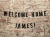 Custom Welcome Home Banner on a Brick Wall