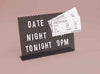 Black magnetic letter board with the message Date Night Tonight at 9pm
