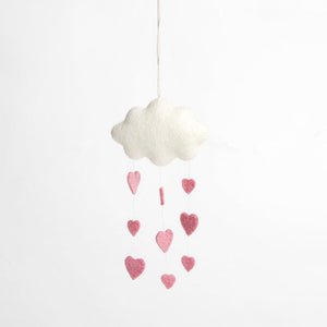 A handmade felt white cloud ornament snowing down three strings of pink hearts