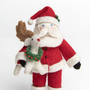 a handmade felt santa ornament holding a white baby rudolph wearing a little green and red wreath.