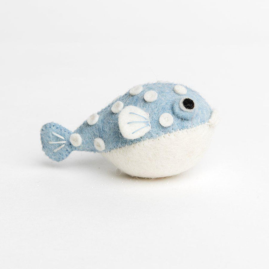 A handmade felt pufferfish ornament with a light blue upper body with white spots and white fins and belly.