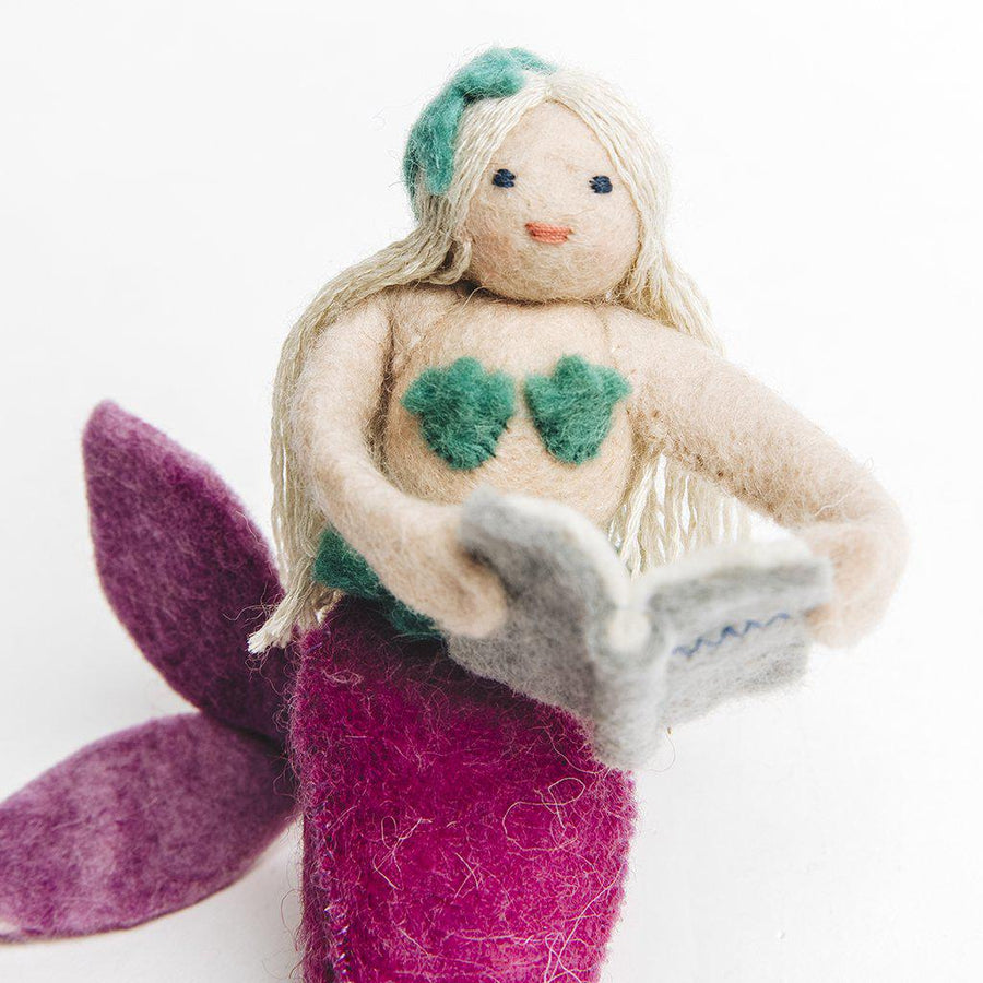 A Craftspring handmade felt mermaid ornament sitting with long bold hair a green bikini top and a purple tail reading a book.