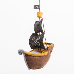 A handmade felt pirate ship ornament with a brown hull and black sails.
