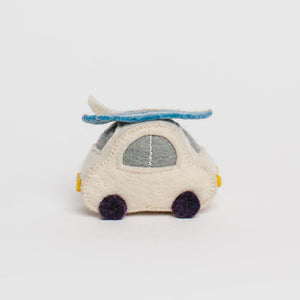 A handmade white volkswagen bug ornament with a light blue surfboard on top grey windows yellow lights and little black wheels.