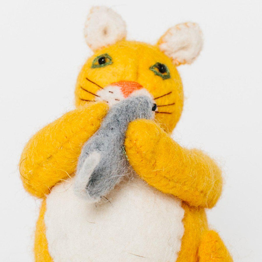 A Craftspring handmade felt cat ornament with yellow fur holding a small grey mouse