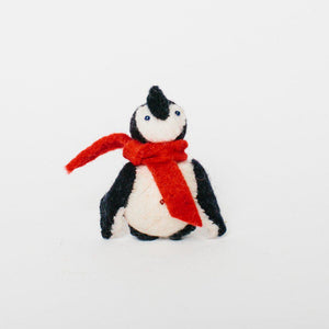 A Craftspring handmade penguin ornament wearing a red scarf