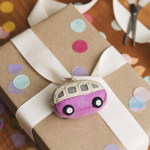 A Craftspring handmade felt pink hippie bus ornament with an embroidered peace sign on the side
