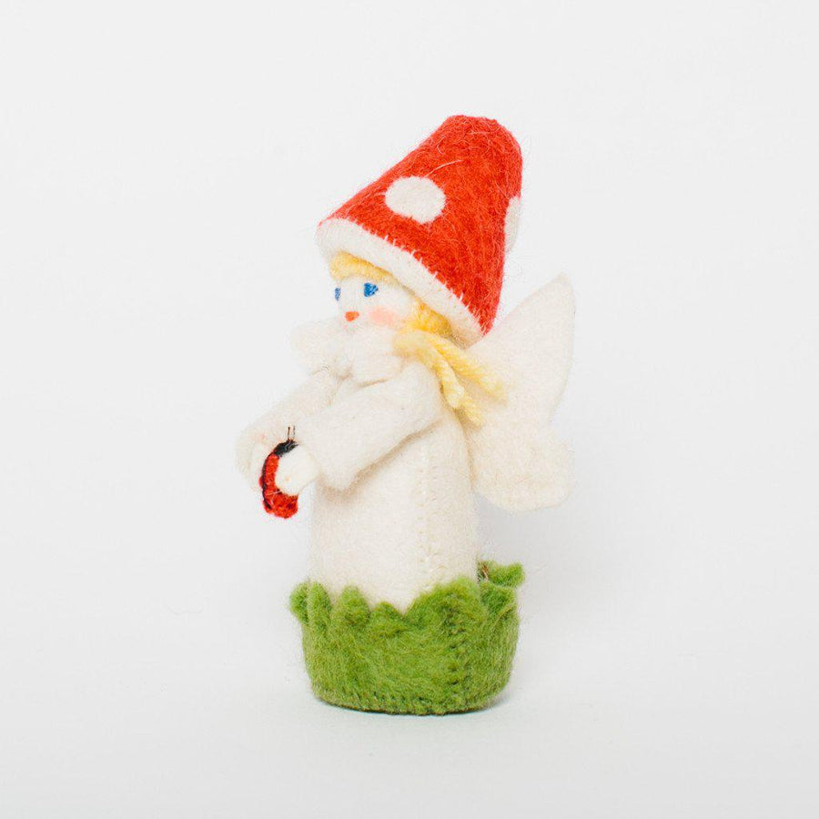 A Craftspring handmade felt fairy ornament wearing a red mushroom cap hat and holding a small lady bug