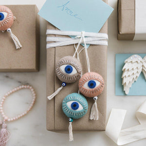 A Craftspring handmade felt spirit eye ornament with beaded eyelashes and a string tassel