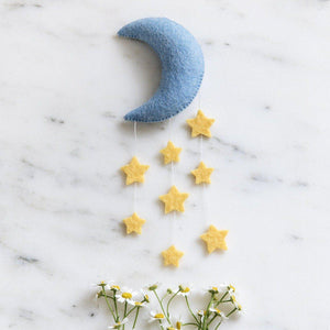 A Craftspring handmade blue felt crescent moon ornament with strings of yellow stars