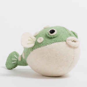 A handmade felt pufferfish ornament with green upper body with white spots and white belly.