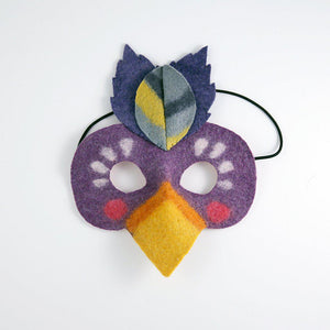 A craftspring handmade felt toucan mask with a purple face orange and yellow beak and blue feathers