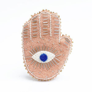 A Craftspring handmade felt pink hamsa ornament with a blue eye and white beading details