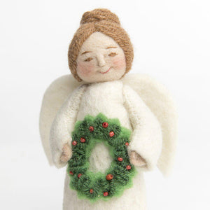 A Craftspring handmade felt angel ornament holding a festive wreath with red bead berries