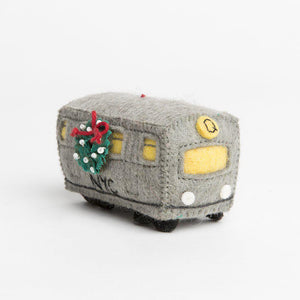 A Craftspring handmade felt Q train subway car ornament with a festive wreath on the side