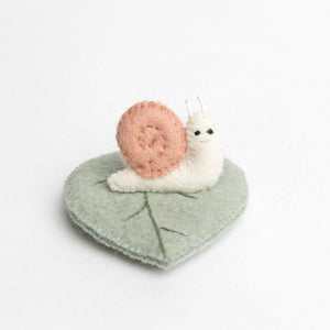 A Craftspring handmade felt snail ornament with a light pink shell sitting on a sage green leaf