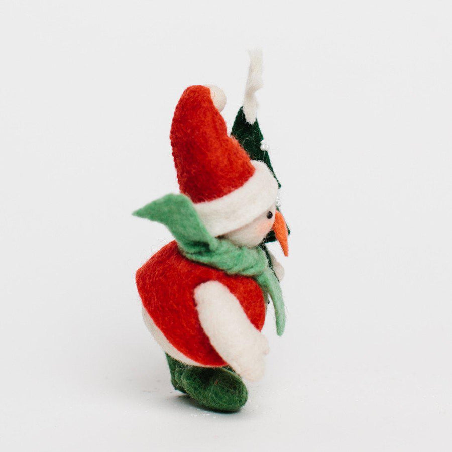 A Craftspring handmade felt snowman ornament with a santa hat, red vest green scarf and boots and holding a small christmas tree