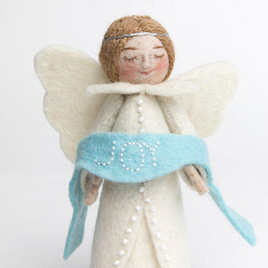 A craftspring handmade felt angel ornament wearing white robes and holding a blue banner with the word joy embroidered across it