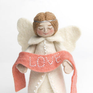 A craftspring handmade felt angel ornament wearing white robes and holding a pink banner with the word love embroidered across it