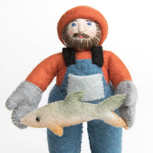 A Craftspring handmade felt fisherman ornament wearing blue overalls a red shirt and cap and holding a salmon