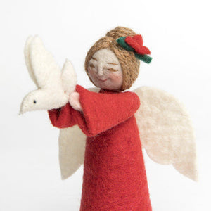 A Craftspring handmade felt angel ornament with her brown hair in a bun with a red flower wearing red robes and holding up a small white dove
