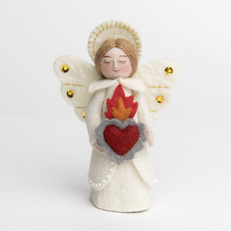 A craftspring handmade felt angel ornament wearing white robes, a halo, sequined wings and holding a flaming heart
