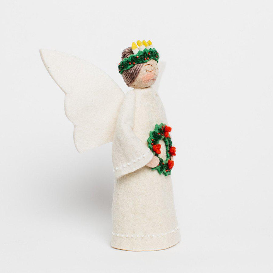 A Craftspring handmade felt santa lucia tree topper angel with her brown hair up in a bun under her crown of candles, wearing white robes and holding a wreath