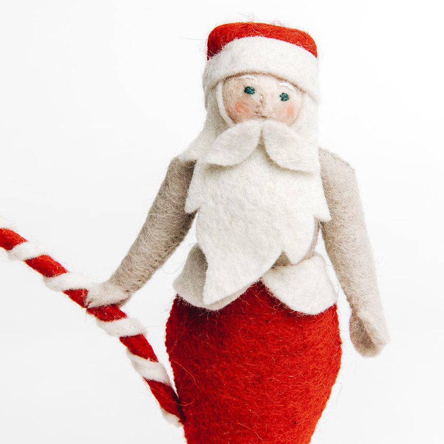 A Craftspring handmade felt santa merman with a red and white tail wearing a santa hat and holding a candy cain