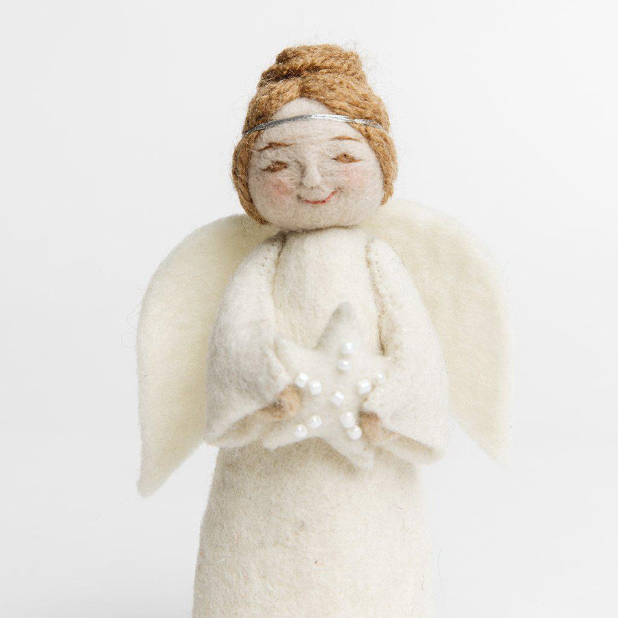 A Craftspring handmade felt angel ornament with blond hair up in a bun wearing white robes a silver circlet and holding a white beaded star